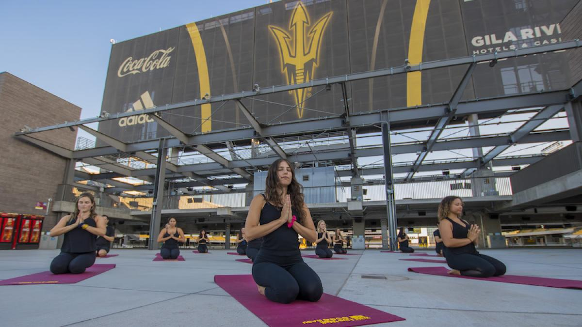Various people performing yoga poses on the rooftop patio of Sun Devil Stadium