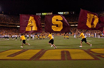 Students running on the Sun Devil Stadium with flags