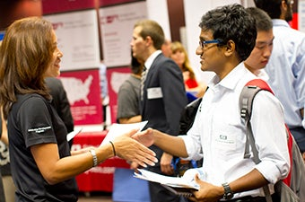 A student shaking an employers hand at a career fair