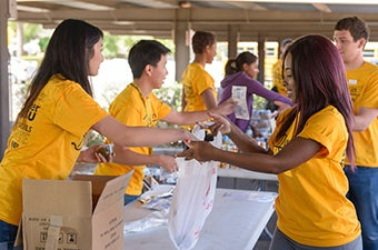 A group of students bagging food during a service event