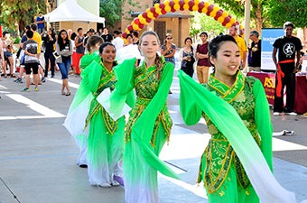 Three students dancing in green outfits