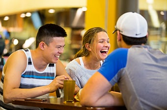 Several students laughing while having a meal