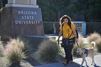 Woman walking with service dog on campus