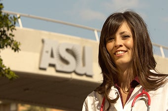 A student posing for a headshot in front of the bridge over University Drive with the ASU logo in the background