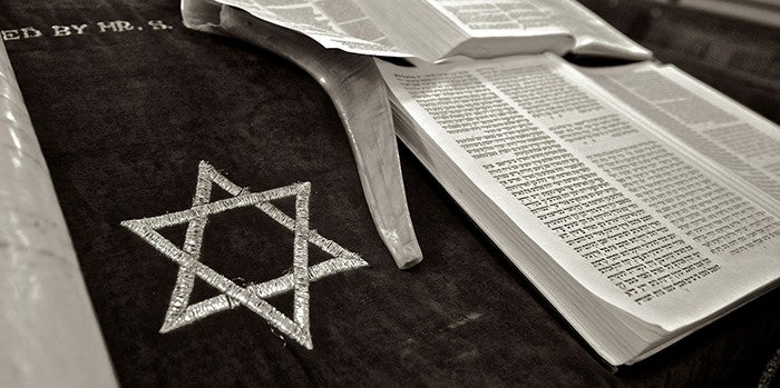 Copy of the Torah lies open on a table, image in black and white