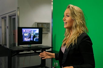 A student delivering a weather report in front of a green screen
