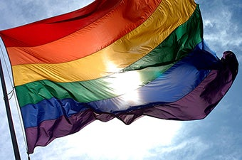 A rainbow flag waving in the wind, backlit by the sun