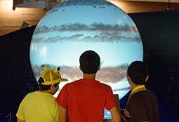 Three students examine a planetary display