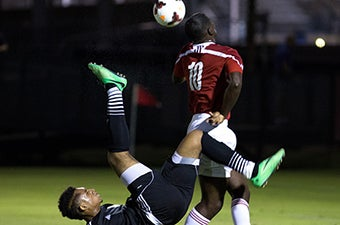 A soccer player in blue attempting to bicycle kick the ball while a student in red and white attempts to play it with his head