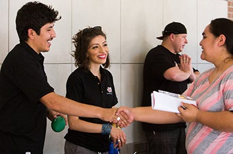 Members of a student organization greeting guests during a campus tabling event