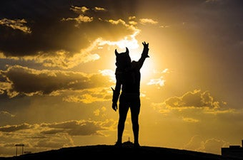 """Silhouette of Sparky mascot against a sunset on """"A"""" Mountain in Tempe, AZ"""