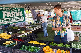 A student looking at fresh vegetables at a farmers market