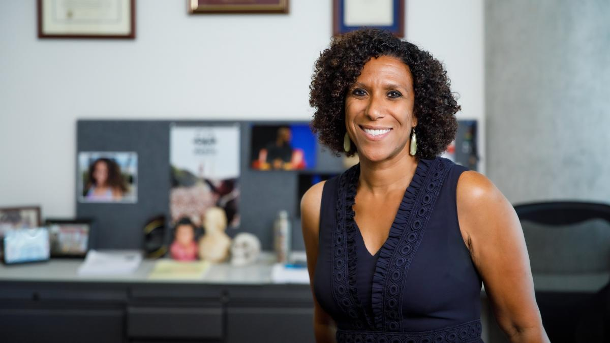Scholar and activist Ayanna Thompson is pictured smiling while posing in her office