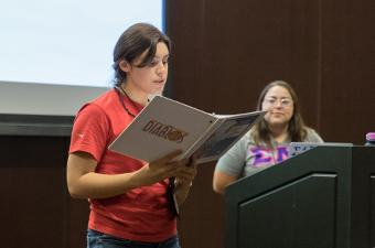 Female student reading from a binder during a workshop