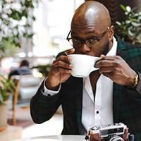 Man looks at camera and sips coffee at a table with a camera nearby