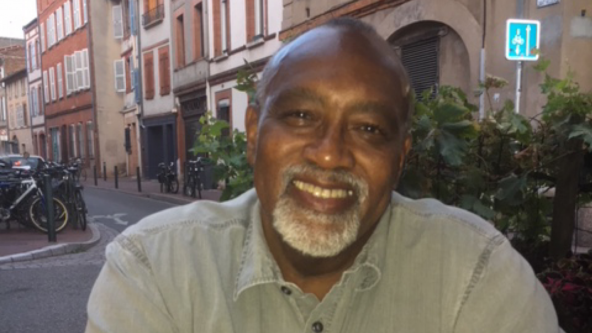 Professor Glenn C. Loury smiles for a picture outside on a city street