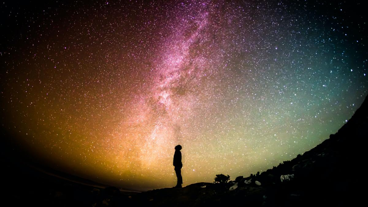 Panoramic view of a starry sky on Earth, with silhouette of a person underneath
