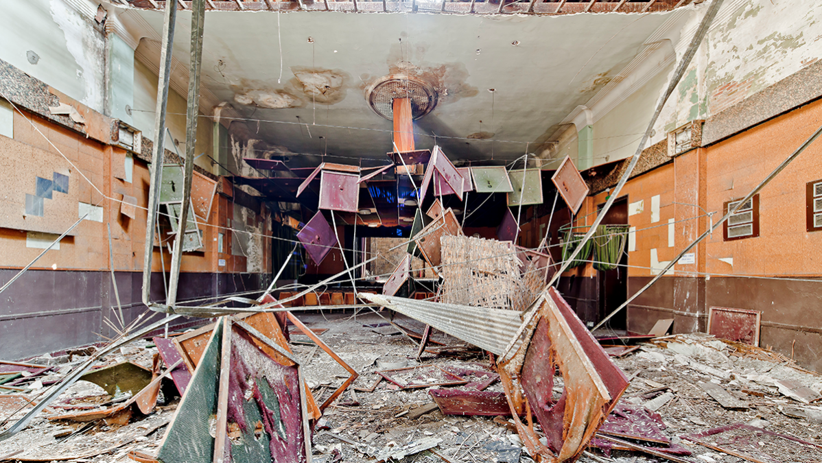 Inside view of an older, reclaimed building space; there is furniture, plaster, and drywall strewn about the room