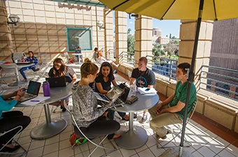 Four students sitting at a table outdoors having a conversation.