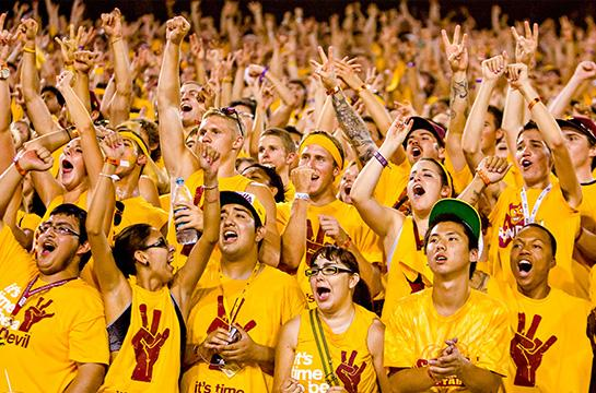 Sun Devils wearing gold cheering at an ASU football game